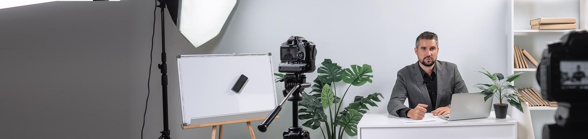 Mann im Anzug sitzt an Schreibtisch und redet in zwei Kameras
